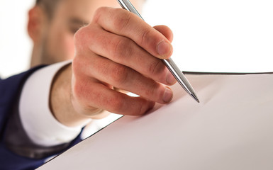 Male hand holds pen near paper document, close up.