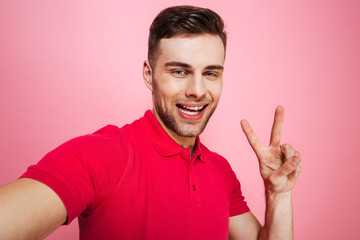Portrait of a smiling young man showing peace gesture