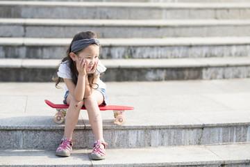 スケートボードに座る女の子
