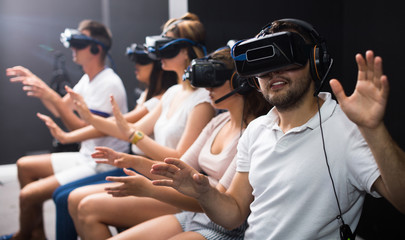Guy is enjoying exciting movie with friends in VR glasses