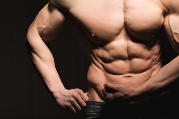 Fitness concept. Muscular and fit torso of young man having perfect abs, bicep and chest. Male hunk with athletic body.