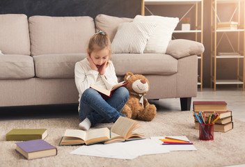 Little girl with book and her favorite toy at home