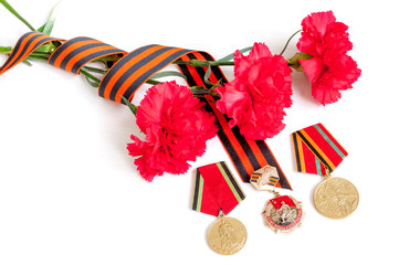 9 May Victory Day festive background - jubilee medals of Great patriotic war with red carnations and St George ribbon