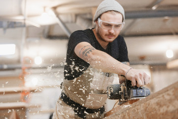 Carpenter working with electric planer on wooden plank in workshop. Hands and planer close up.