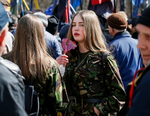 A supporter of Ukraine's far-right parties and movements eats a lollipop as she attends a protest against oligarchs in Kiev