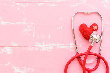 World health day, Healthcare and medical concept. Red heart with Stethoscope, notepad, thermometer and yellow Pill on Pastel white and pink wooden background.