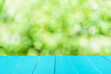 Pastel blue wooden table and blur nature tree green background with spring or summer.