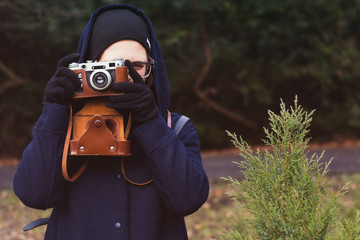 Young woman in hoodie holding retro photo camera and taking photo in the forest.  Autumn nature on background. Toned photo.