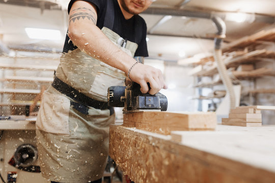 Carpenter working with electric planer on wooden plank in workshop. Craftsman makes own successful small business.