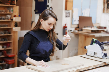 young happy women standing at a work bench in a carpentry workshop, process a tree a varnish. Family business. startup business. young specialist designer.