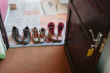 modern casual boots on the floor at hotel doorstep. Pink white and black color, dirty after long travel