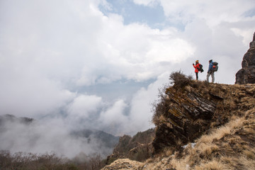 Hikers couple with backpacks relaxing on top of  mountain enjoying and make pictures view of valley above clouds