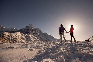 Travel couple relaxing on top of snow high mountain and enjoying view of Fishtale mountain, sunrise time, strong travel concept
