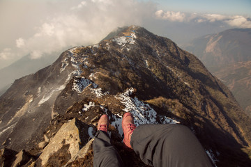 Legs of traveler hiker staying high mountain top above clouds and valley in hiking travel. Dizzy view, Freedom concept