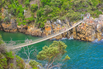 Spoed Fotobehang Zuid Afrika The Suspension Bridge over the Storms River Mouth within Tsitsikamma National Park, Eastern Cape, near Plettenberg Bay in South Africa. It is an important tourist destination along the Garden Route.