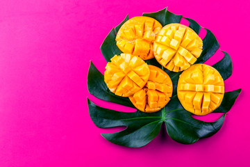 Poster Rose Creative layout made of summer tropical fruits mango and tropical leaves on pink background. Flat lay. Tropical food concept.
