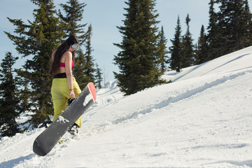 Snowboard female walking with board on snow mountain. Winter sport holiday mountains sky resort