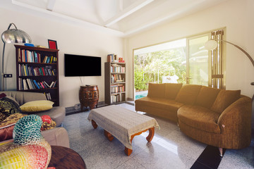 Luxury Tropical  Villa Reception living room with big open glass doors in jungle, Thailand, Asia. Books, sofa, TV on the wall