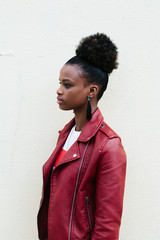 portrait of cheerful black teenage girl with healthy-looking skin and voluminous african hair, dressed in red Leather Jacket.