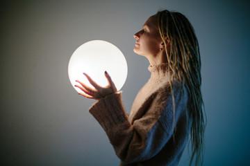 Young woman wearing blond dreadlocks keep glowing ball lamp