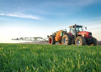 Unkrautbekämfung im Frühjahr, roter Traktor mit Feldspritze im jungen Getreidebestand