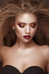 Beautiful blond model: curls, bright makeup and red lips. The beauty face.