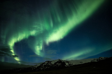Northern lights aka Aurora Borealis glowing on the sky with mountains in Iceland