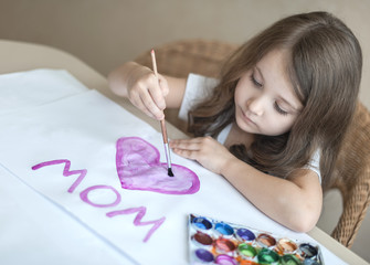 Child making homemade greeting card. A little girl paints a heart  on a homemade greeting card as a gift for Mother Day. Traditional play concept. Arts and crafts concept
