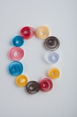 Letter O made of red, pink, blue, yellow, white, brown paper quilling spirals