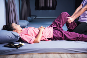 Thai leg massage to Asian tan woman