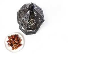 Ornamental dark Moroccan, Arabic lantern and plate with date fruits on white table. Greeting card for Muslim holy month Ramadan Kareem. Festive background. Empty space. Flat lay, top view.