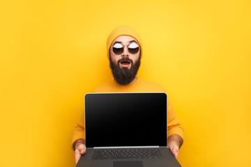 Trendy man advertising laptop