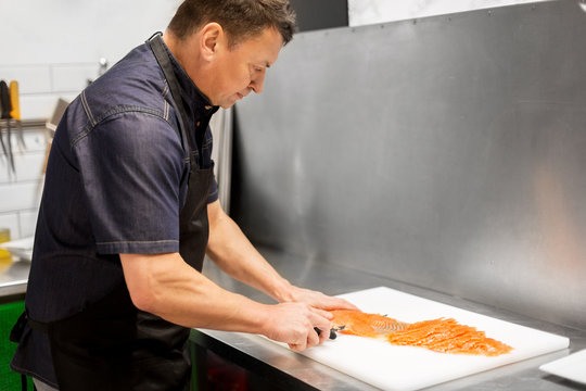 food sale, small business and seafood cooking concept - male or chief slicing smoked salmon fillet at fish shop or restaurant kitchen