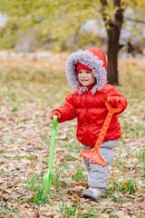 A small kid with a rake and a shovel walks in the park
