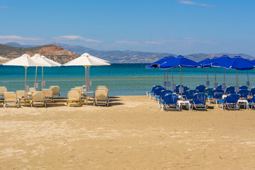 Umbrellas and sunbeds on beach in summer. Naxos island. Cyclades, Greece.