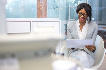 Smiling business woman sitting on chair in office and reading paper document