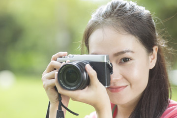 Young asian girl taking photo outdoors with digital camera
