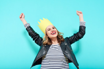 Party girl in leather jacket and party crown on pastel blue background celebrating and dancing. Party, having fun, dancing, laughing.