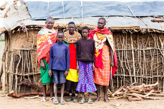 Massai family looking in camera in front of hut