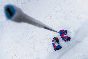 The gloves and hockey stick lay on the snow