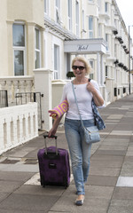 Single woman walking alone searching for accommodation at a seaside resort,Pulling a suitcase and holding a towel.