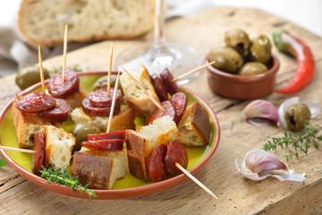 Spanische Pinchos: Angebratene scharfe Chorizo Paprikasalami auf geröstetem Weißbrot serviert