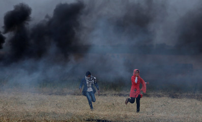Palestinian girls runs for cover during clashes with Israeli troops at the Israel-Gaza border, in the southern Gaza Strip