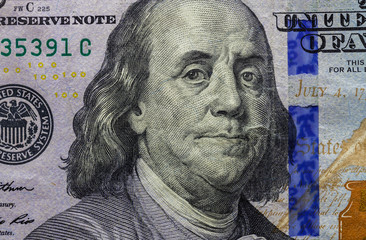 Close up of one hundred dollar banknotel showing portrait of Benjamin Franklin