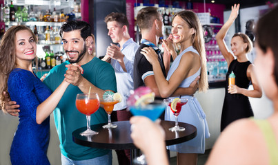Female with man are dancing in bar