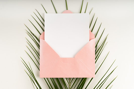 Minimal composition with a pink envelope, white blank card and a palm leaf on a white background. Mockup with envelope and blank card. Flat lay. Top view.