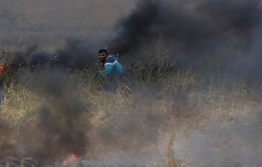 Palestinian takes cover during clashes with Israeli troops at the Israel-Gaza border, in the southern Gaza