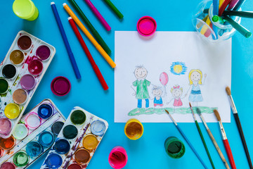 Childrendrawing pencil happy family mom, dad, son, daughter sunny day on the lawn and paint accessories, brush, felters gouache, watercolor on a blue background flat  lay top view from above