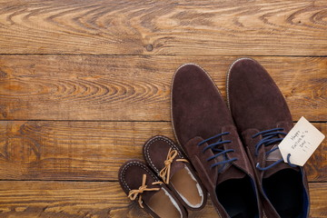 Male and child shoes on rustic wood background