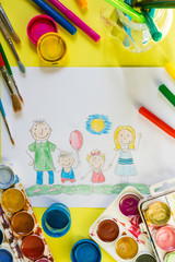 Childrendrawing pencil happy family mom, dad, son, daughter sunny day on the lawn and paint accessories, brush, felters gouache, watercolor on a yellow  background flat  lay top view from above